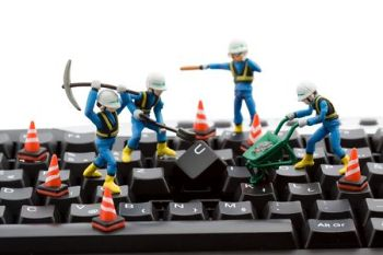 Toy work men digging up a keyboard indicating service and maintenance